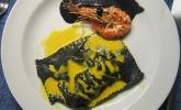 Schwarze Ravioli mit Garnelenfüllung an gelber und schwarzer Sauce