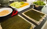 5. Schritt: Alle Zutaten – den Sushi-Reis, Gurke, Mango, Avocado, die Erdnüsse und den Rucola – um die Bambusmatten mit je einem Noriblatt bereitstellen.