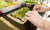 Schritt 10: Nun das Ende des Algenblatts mit Wasser beträufeln, sodass das Noriblatt am Ende des Rollens beim Verschließen haften bleibt. Den Sushi Burrito von unten nach oben rollen. Dabei die Rolle fest andrücken.
