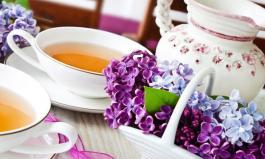 Tischdeko im Frühling: Blumen, Kerzen und weißes Porzellan